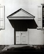 A black and white photograph of a meeting house doorway.
