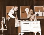 REA director John Carmody demonstrating the advantages of electrical appliances during a farm equipment tour, circa 1938.