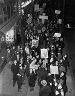Aerial view of a group of picketers holding signs, in front of a radio station.