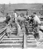 Men cutting and laying steel rails
