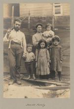 A man, his wife, and four children pose for this photograph