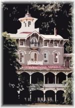 Asa Packer Mansion. Pink and white mansion with cupola and two porches with columns and arches stretched across the length.