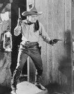 Tom Mix in Cowboy costume with guns in both hands.