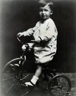 Jimmy Stewart riding a tricycle.