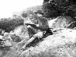 Photograph of Waud as he sits on a boulder with a sketch book propped on his knee.
