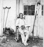 War veteran John Burns seated outside in a rocking chair with his musket propped near the door to a building.