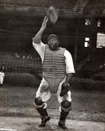 Here Josh Gibson, the 'Black Babe Ruth', famous Negro League baseball player, wearing a white home uniform covered with dirt, and catchers' gear, throws his mask up into the air.