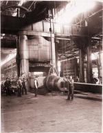 Gelatin printing out paper print, mounted on board of workers processing a 90-ton ingot using a 10,000-ton forging press at Carnegie Steel Company's Homestead Steel Works.'