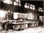 Homestead Steel Works and workers standing next to a railroad flat car that carries a large steel product.'