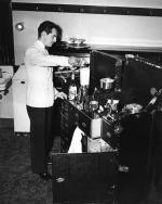 Waring standing, with his blender invention on top of his travel trunk.