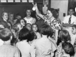 Black and white image of a  teacher holding a light bulb in her hand, while surrounded by her amazed students