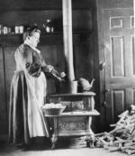 Black and white image of woman at the stove.