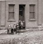 A group of immigrant children stand in a doorway in Johnstown.'