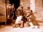 Men sucking freshly pressed juice fresh from an apple press through rye straws.