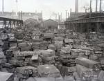 Photograph shows piles of steel ingots on the exterior of the steel plant.'