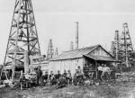 A group of aproximately twenty workers pose in front of a shed and several oil derricks.