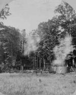 A derrick is connected to a metal tank by a series of pipes. Visible in the photo, escaping from the well and the tank, is a smoky mist.