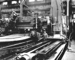 An interior view of the Nicetown plant, Midvale Steel, featuring workers and machining armor.'