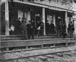 Image of Hanover Junction with passengers standing along the porch of the station.
