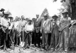 Governor Pinchot, dressed in a suit, is flanked on either side by farmers, many dressed in overalls and carrying scythes.