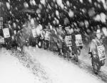 Men wearing picket signs marching in the snow.