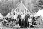 A group of about 25 young men are posed in front of a tent.