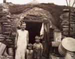 Family standing outside the entrance of their coke oven home