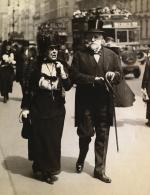 Black and White photograph of Mr. and Mrs. Henry Clay Frick.  He wears a top hat and carries a cane. She is wearing hat and glove. Both are in formal dress walking together at an Easter parade.