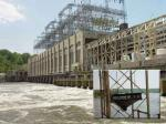 A photograph of the Conowingo Dam, with a second, close-up shot of the fish elevator and a third of a school of fish within the cage of the elevator.