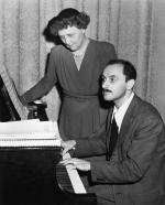 "American composer Marc Blitzstein (1905-1964), shown demonstrating on the piano a passage from his ""Airborne Symphony."" A young woman looks on."