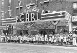 Image of the exterior of the theater with a large group of adults and children standing in front.