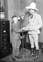 Full-length portrait of actor Tom Mix wearing a cowboy outfit, standing next to a microphone and shaking hands with an unidentified boy in a room at the offices of Chicago Daily News radio station WMAQ in Chicago, Illinois. A WMAQ logo is visible on the microphone.