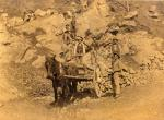 One worker stands beside a mule and an Ore Wagon in the foreground of this sepia photograph, as five other male workers stand at different levels on the hillside, holding their tools.