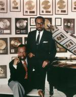 Color photograph of Kenny Gamble and Leon Huff at the piano, with the wall of gold  albums in the background. Reflections of Gold records can be seen in the top of the piano.
