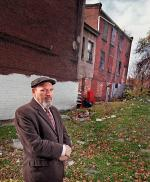 Playwright August Wilson standing in front of his boyhood home (far right) on Bedford Street in Pittsburgh.