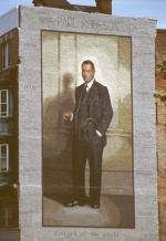 Mural painting of Robeson, standing, wearing a three pice suit.'