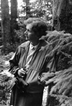 Rachel Carson leaning against a tree, her face turned to the camera.