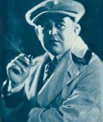 Head and shoulders image of Victor Schertzinger, wearing a suit, cap, and smoking a cigarette.