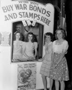 "Two women stand on the inside of a Victory booth, which boasts a sign, ""Buy War Bonds and stamps here."" Two young women stand at the window on the outside of the booth."