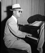 Image of Earl Hines playing the piano. He is wearing a suit, hat, and dark sunglasses.