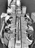 Two rows of women, sit on opposite sides of a huge table as they work on an assembly line.