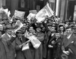 Crowd holding up V - E Day headlines