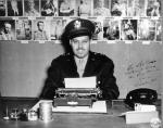 Frank Bolden in uniform at desk behind typewriter