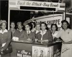 A group of women dressed in military clothing stand under sign, which reads 'Back The Attack-Buy Bonds.' On the far right is Ruth Gwynnon, who organized this campaign, ca. 1939-1945.