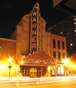 Evening view of the exterior of the theater in lights.