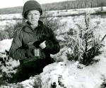 Uniformed soldier wearing a helmet, inside a fox hole, preparing some thing to drink. The ground is covered in snow.