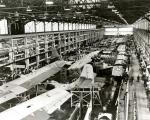 Interior photograph of a Naval aircraft factory filled with planes and employees