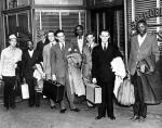 Bayard Rustin (fourth from right) stands with a group of people, some holding baggage, posing for a departure photo.