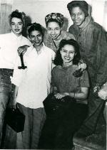 Five women workers pose for a photograph.'