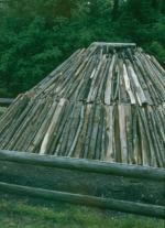 Image of a Charcoal kiln made of logs.